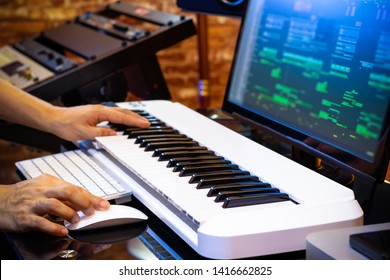 male professional music producer hands arranging a song on midi keyboard and computer in home studio. music production concept