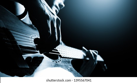 male professional musician playing acoustic guitar on stage, music background