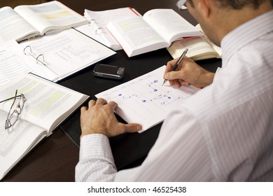 Male professional sitting at desk in office drawing a flow-chart and being busy studying books, rear view.