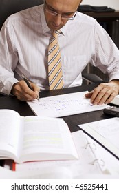 Male professional sitting at desk in office drawing a flow-chart and being busy studying books, front view.