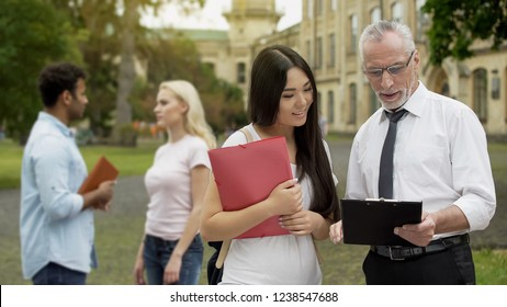 Male professor discussing thesis with asian female student near university