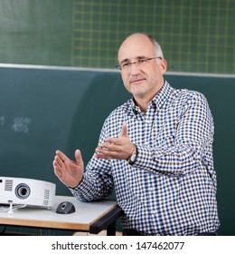 Male professor with projector and mouse gesturing in classroom