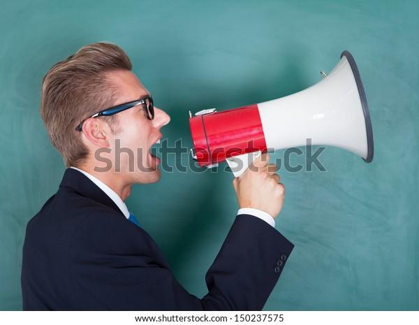 Male Professor Shouting Though Megaphone Against Chalkboard