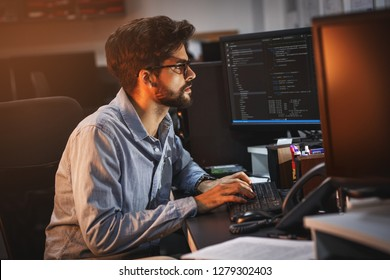 Male programmer working on new project.He working late at night at the office.