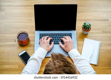 A male programmer works in front of a laptop screen in a bright office or remotely from home. Workplace