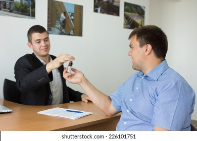 Male Property Agent Giving the House Key to Middle Age Male Client at the Office.