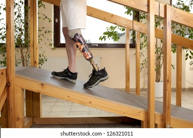 Male prosthesis wearer training to climb a slope unaided in a special parkour or interior area where surfaces have been laid out to simulate realistic environmental situations