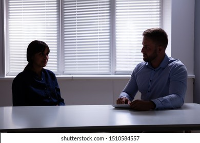 Male Psychologist Talking With Female Patient Or Asking Personal Information In Dark Room
