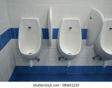 Male public toilet with a blue floor and white urinals