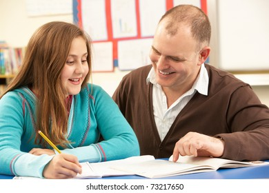 Male Pupil Studying in classroom with teacher