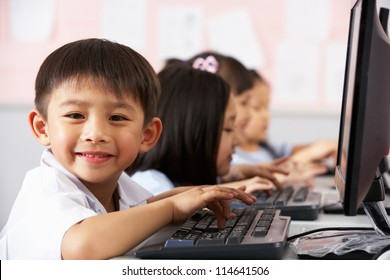 Male Pupil Using Keyboard During Computer Class In Chinese School Classroom