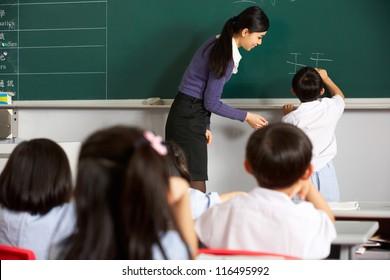 Male Pupil Writing On Blackboard In Chinese School Classroom