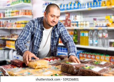 Male purchaser buying kidney beans in local supermarket