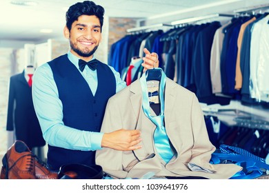 Male purchaser demonstrating his choice of suit in store