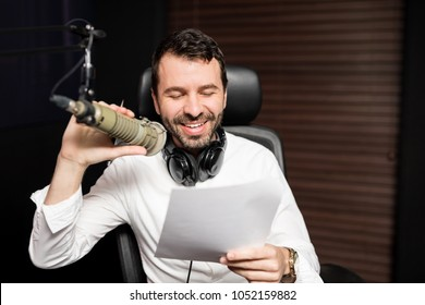 Male radio broadcaster talking on mic with a paper in hand