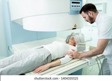 Male radiologist comforting patient who is undergoing for MRI scan of her head in the hospital.