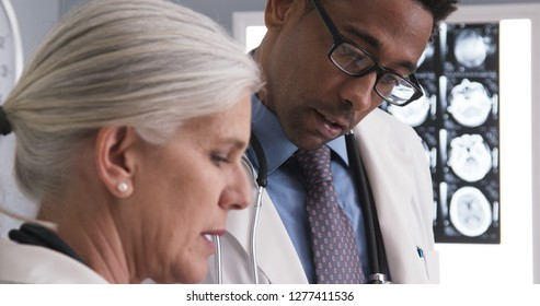 Male radiologist consulting with senior colleague about patients ct scans