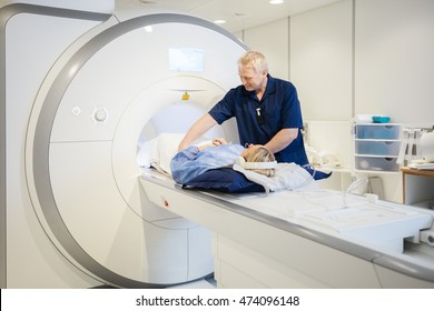 Male Radiologist Preparing Young Woman For MRI Scan