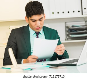 Male is reading documents about the transaction in office.