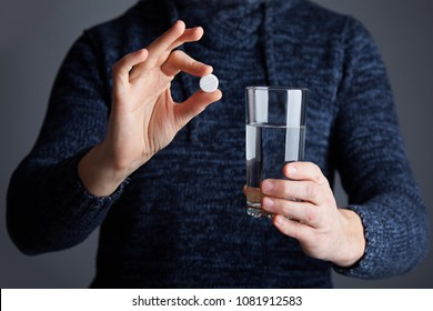 Male ready to dissolve the pill in water. Soluble white pill and a glass of water in his hands. Effervescent tablet aspirin in glass of water
