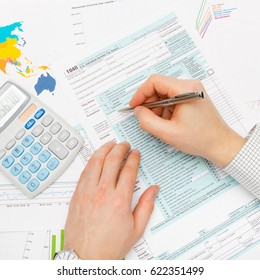 Male ready to fill out 1040 US Tax Form with calculator next to his left hand - close up shot