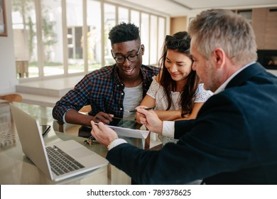 Male real estate agent offering to buy a new house to young couple during a meeting. Realtor presenting technical documentation to owner couple.