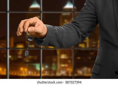 Male realtor gives apartment key. Night office worker holding key. Choose the right door. Knock and open.