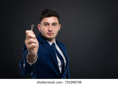 Male realtor holding key from apartment after renting it on dark background with copyspace