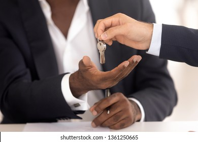 Male realtor real estate agent hand give keys to african american new home owner make sale purchase deal, black customer renter buyer tenant buy house, mortgage investment, property ownership concept