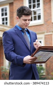 Male Realtor Standing Outside Residential Property