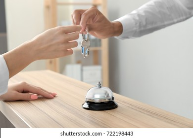 Male receptionist giving key from hotel room to client