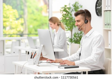 Male receptionist with headset at desk in office