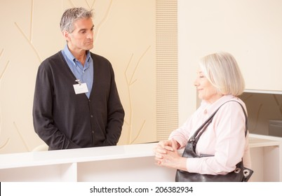 Male receptionist receiving senior woman at reception desk in hospital waiting room.