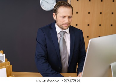 Male receptionist wearing blue business suit types on his computer at front desk