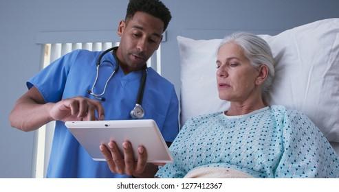 Male registered nurse showing ill elderly woman electronic pad