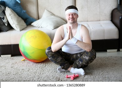 Male relaxing human body traning yoga aganist home background. Reassures his thoughts thinks of good brings up fortitude concept.