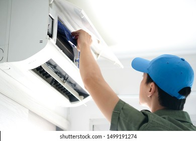 Male repair air conditioner at room, He is air technician , mechanic , engineer. Maintenance air conditioner myself.