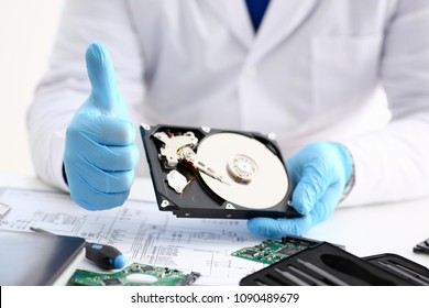 Male repairman wearing blue gloves is holding hard drive from computer laptop in hands show OK thumbs up. Performs diagnostics performs urgent repairs recovery of lost data during deletion HDD closeup