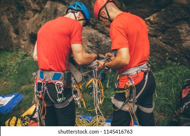 Male rescuer climbers with equipment preparing for action. Back view