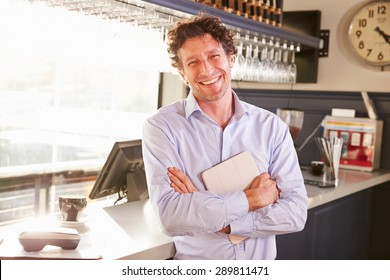 Male restaurant owner holding digital tablet, portrait