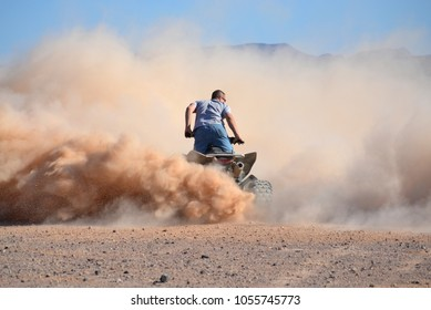 Male rider on quad in dust cloud in desert