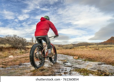 a male riding a fat bike across a stream in Red Mountain Open Space, Colorado , late fall scenery