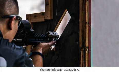 Male with rifle in hands aimimg target through one of the hole of VTAC 9-holes shooting barricade in tactical shooting competition