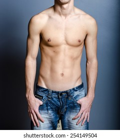 Male ripped body with hands in pockets and nipple piercing over a blue background