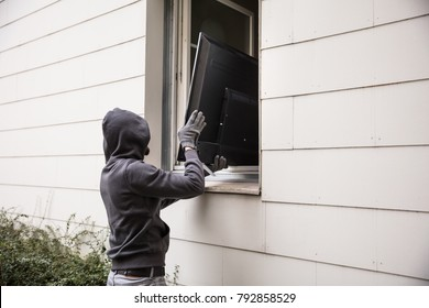 Male Robbers In Hoods Stealing Television Through House Window