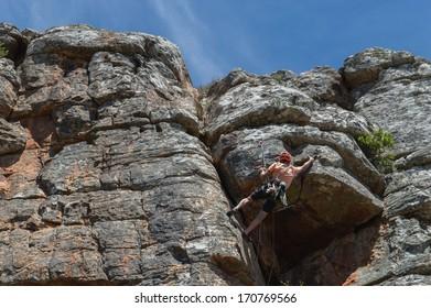Male rock climber ascending steep climb