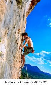 male rock climber climbs on a rocky wall