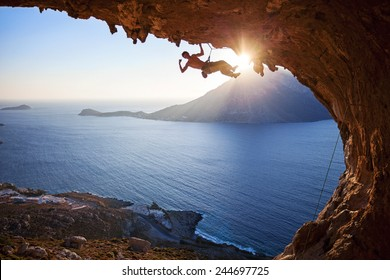 Male rock climber flexing his bicep while hanging on one arm at sunset. Climbing along roof in cave, Kalymnos, Greece.