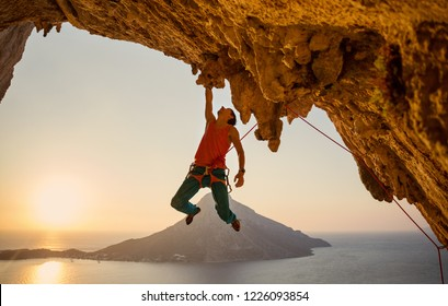 Male rock climber hanging on cliff with one hand at sunset. Kalymnos island,Greece.