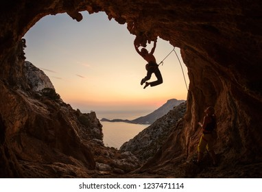 Male rock climber hanging on challenging route on cliff at sunset, female climber belaying him